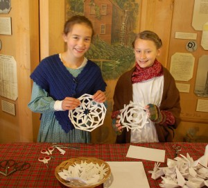Children enjoy cutting paper snowflakes to take home and decorate for their tree!