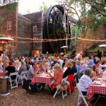 Guests enjoy a farm-to-table dinner at the foot of the great water wheel.